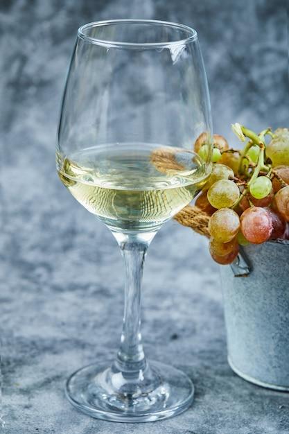 Balde de uvas e um copo de vinho na superfície azul. Foto gratuita
