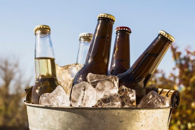 Balde de vista frontal com cubos de gelo frio e garrafas de cerveja Foto gratuita