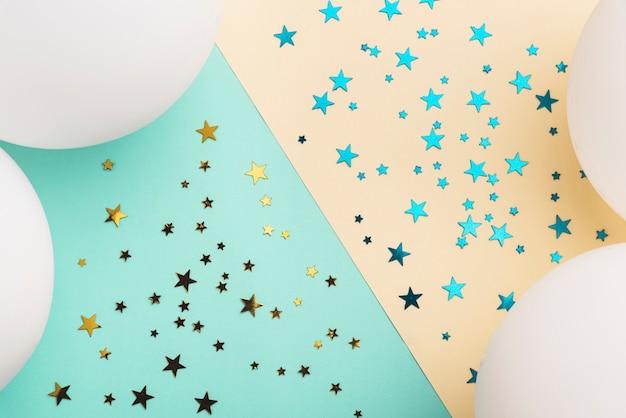 Balões brancos e estrelas de confete em fundo colorido Foto gratuita