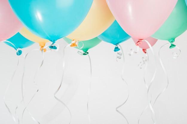 Balões coloridos com fitas em fundo cinza Foto gratuita