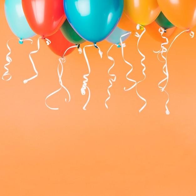 Balões coloridos com fitas em fundo laranja, com espaço de cópia Foto gratuita
