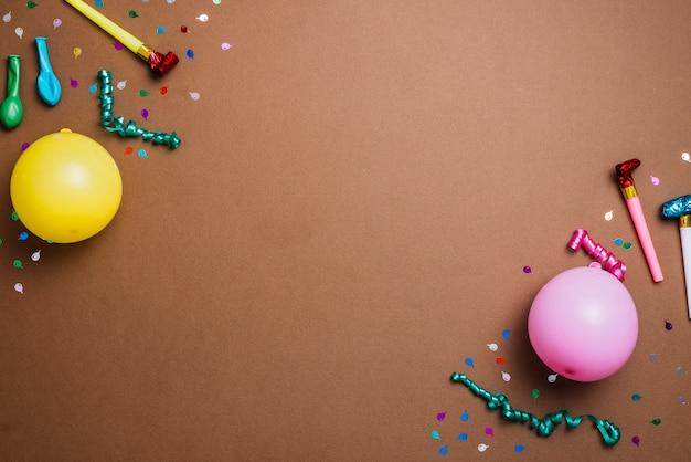 Balões; confete; flâmulas e ventilador de chifre de festa no canto do pano de fundo Foto gratuita