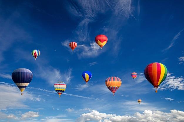Balões de ar quente coloridos voando sobre nuvens brancas e céu azul. Foto Premium