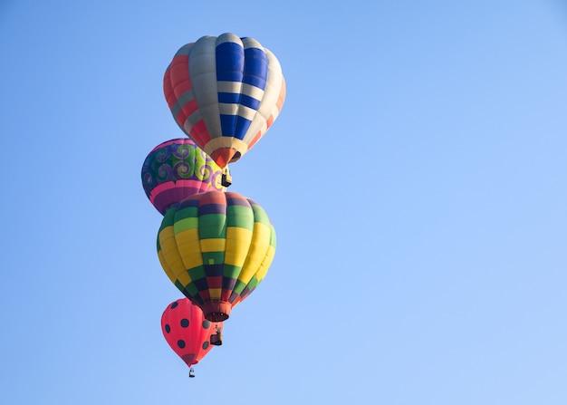 Balões de ar quente voando no céu azul Foto Premium