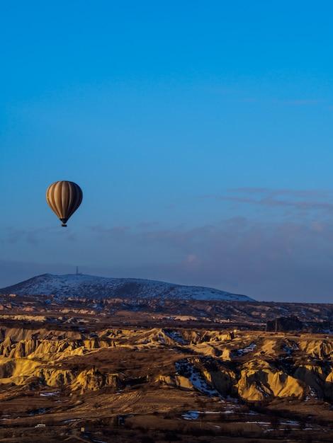 Balões de ar quente voando sobre a montanha na capadócia goreme national park turquia Foto Premium