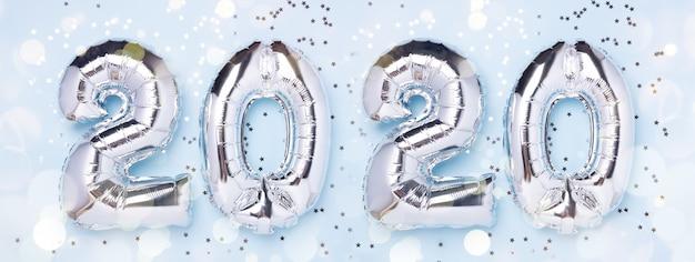Balões de prata em forma de números 2020 e confetes em azul Foto Premium