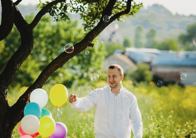Balões de sabão voam em torno de um homem em pé sob uma árvore verde Foto gratuita