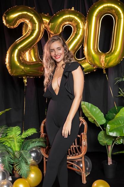 Balões dourados do ano novo 2020 e menina bonita Foto gratuita