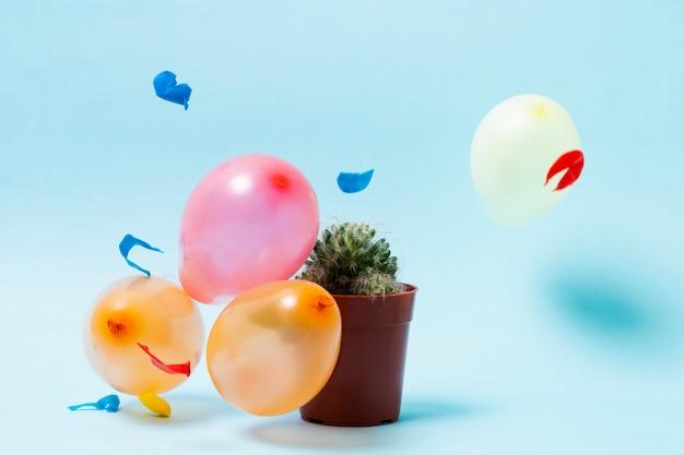 Balões e cactos em fundo azul Foto gratuita