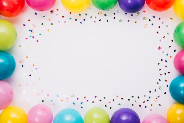 Balões e quadro de confetes com espaço para escrever texto Foto gratuita