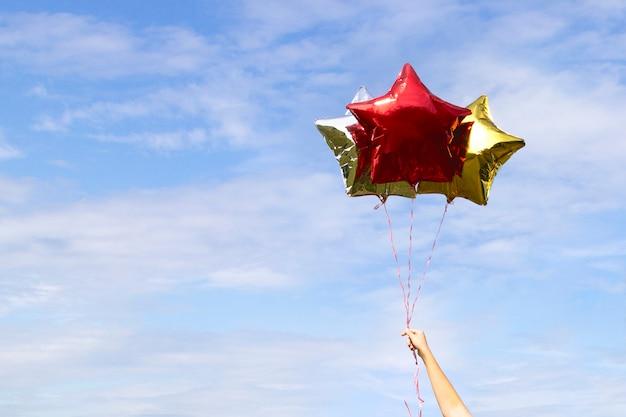 Balões em forma de estrela brilhantes dourados coloridos no céu com nuvens Foto Premium