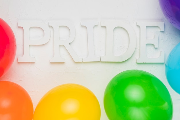 Balões multicoloridos e palavra orgulho Foto gratuita