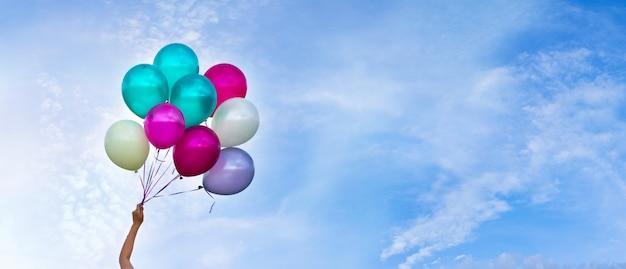 Balões multicoloridos, fundo do céu, conceito de feliz aniversário no verão e festa de lua de mel de casamento Foto Premium