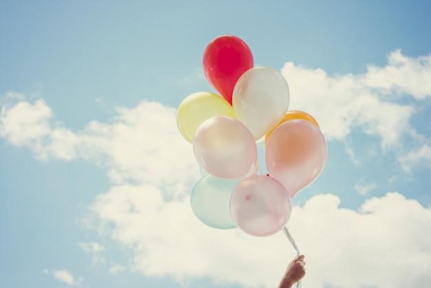 Balões segurando a mão de cores diferentes Foto gratuita
