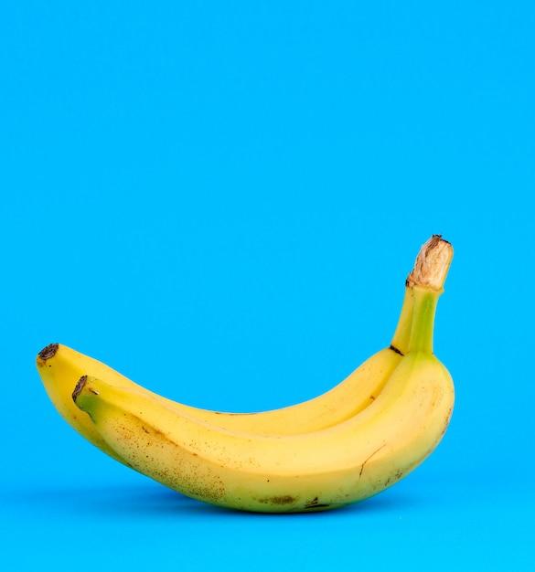 Banana amarela madura sobre um fundo azul, copie o espaço Foto Premium