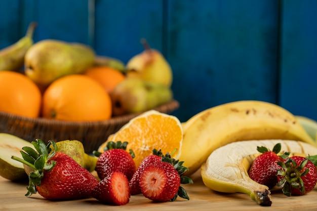 Banana, pêra fatiada, morangos e laranjas em uma parede azul Foto gratuita