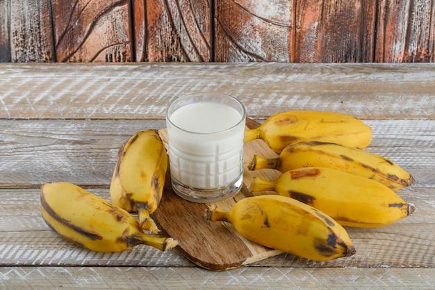 Bananas com leite na tábua de madeira e corte, vista de alto ângulo. Foto gratuita