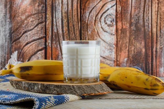 Bananas com leite, vista lateral da tábua de corte em tapete de madeira e kilim Foto gratuita