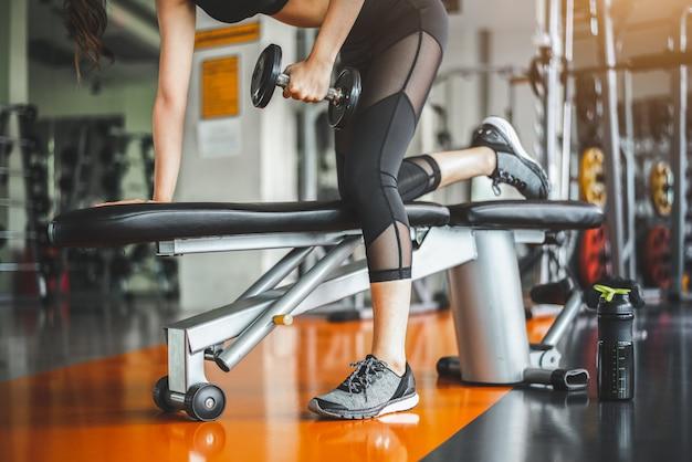Banco da jovem mulher que pressiona com pesos no gym da aptidão. tríceps de trabalho e levantamento de peso no peito. Foto Premium