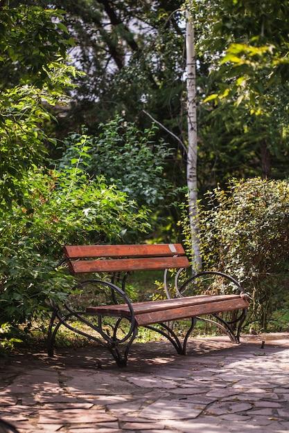 Banco de jardim, feito de madeira e ferro fundido, sente-se no banco, férias de verão Foto Premium