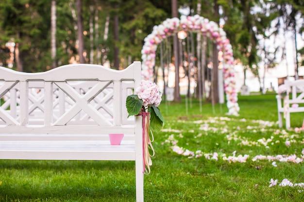 Bancos de casamento e arco de flores para cerimônia ao ar livre Foto Premium