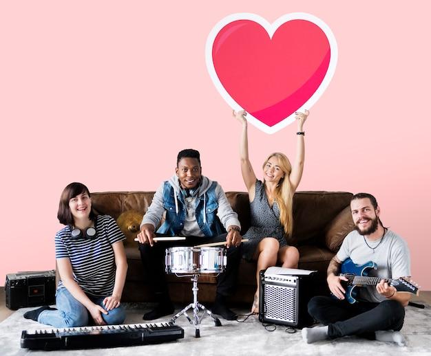 Banda de músicos segurando um emoticon de coração Foto gratuita