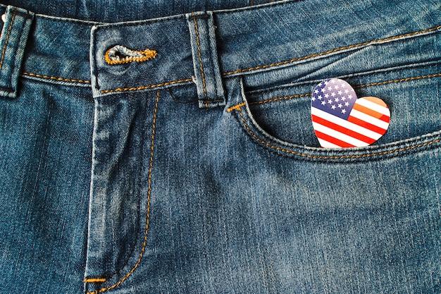 Bandeira americana da forma do coração no bolso das calças de brim da sarja de nimes Foto gratuita