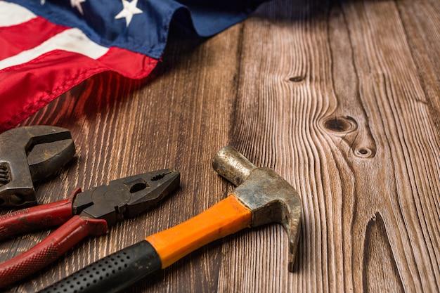 Bandeira americana e ferramentas perto do capacete conceito do dia do trabalho. Foto gratuita