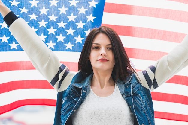 Bandeira americana e mulher com as mãos para cima Foto gratuita