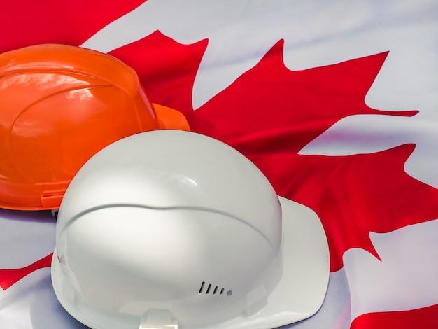 Bandeira canadense e dois capacetes de proteção. fechar-se Foto Premium