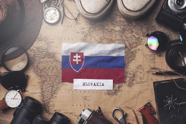 Bandeira da eslováquia entre acessórios do viajante no antigo mapa vintage. tiro aéreo Foto Premium
