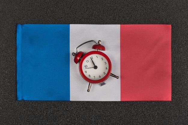 Bandeira da frança e despertador vintage, close-up. hora de aprender francês Foto Premium