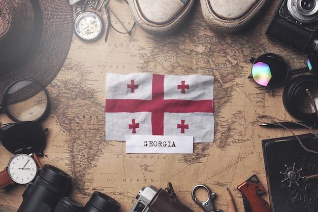 Bandeira da geórgia entre acessórios do viajante no mapa antigo do vintage. tiro aéreo Foto Premium