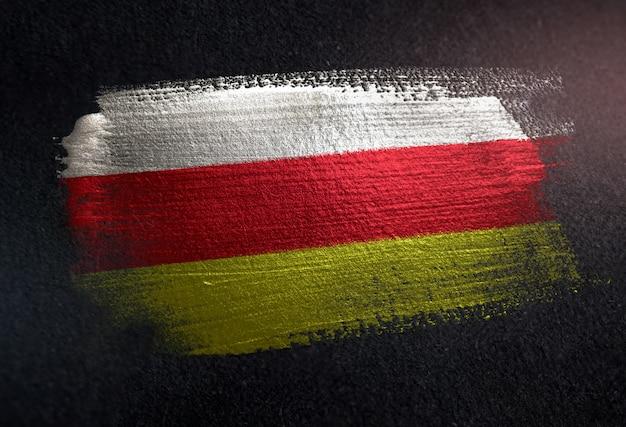 Bandeira da ossétia do norte-alania feita de tinta de escova metálica na parede escura do grunge Foto Premium