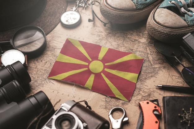 Bandeira da república da macedônia entre acessórios do viajante no antigo mapa vintage. conceito de destino turístico. Foto Premium