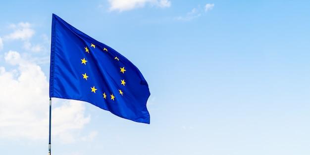 Bandeira da união europeia contra o céu azul acenando Foto Premium