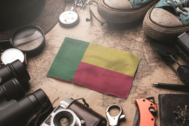 Bandeira de benin entre acessórios do viajante no mapa antigo do vintage. conceito de destino turístico. Foto Premium