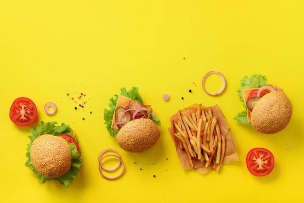 Bandeira de fast-food. hamburgueres suculentos da carne com carne, tomate, queijo, cebola, pepino e alface no fundo amarelo. Foto Premium
