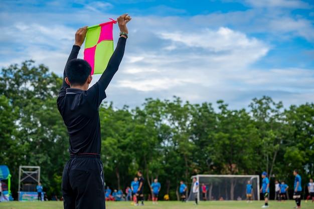 Bandeira de futebol na mão do árbitro assistente de futebol Foto Premium