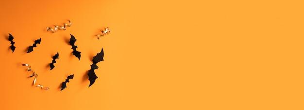 Bandeira de halloween com bastões pretos em uma superfície alaranjada, vista superior. Foto Premium