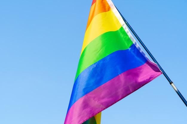 Bandeira de ondulação lgbt no céu no mastro de bandeira Foto Premium