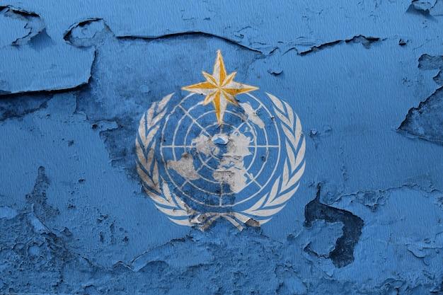 Bandeira de organização meteorológica mundial pintada na parede rachada do grunge Foto Premium