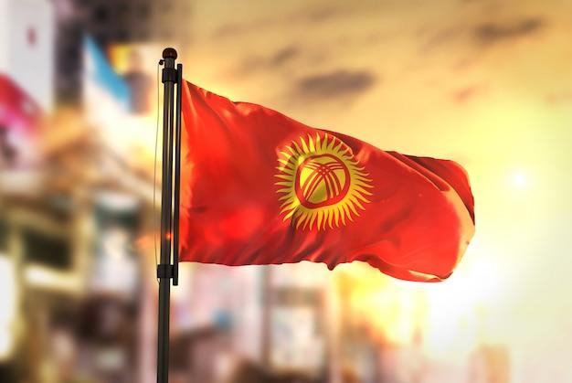Bandeira de quirguistão contra a cidade fundo borrado no amanhecer luz de fundo Foto Premium