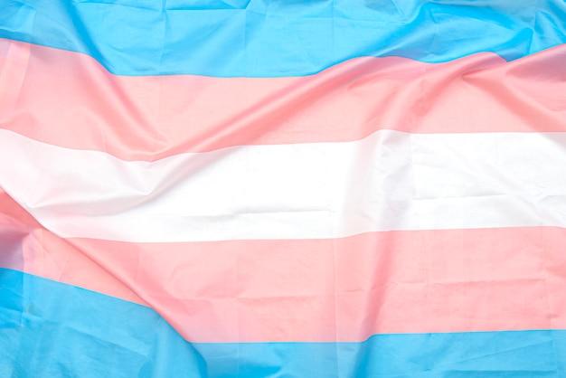 Bandeira de tecido transgênero com tiras brancas, rosa e azuis. bandeira do orgulho transgênero como plano de fundo ou textura Foto Premium