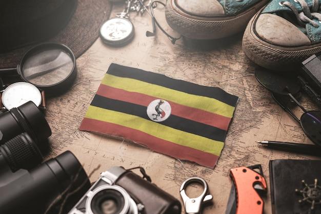 Bandeira de uganda entre acessórios do viajante no mapa antigo do vintage. conceito de destino turístico. Foto Premium