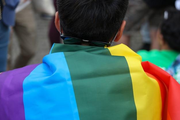 Bandeira do arco-íris de lgbt coberta sobre para trás de um homem que ande na parada. Foto Premium