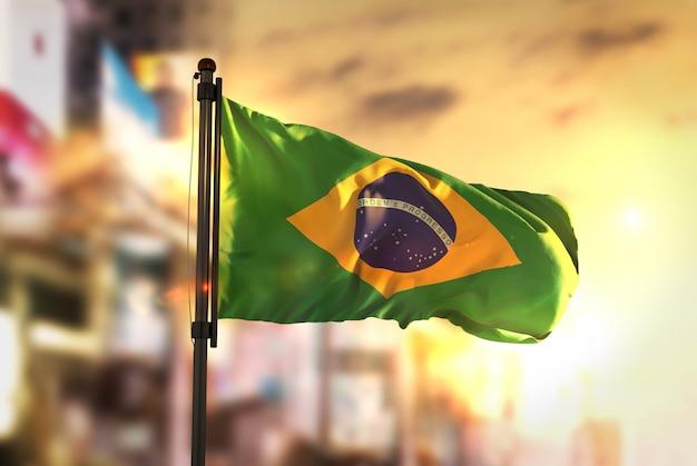 Bandeira do brasil contra a cidade fundo borrado no amanhecer luz de fundo Foto Premium