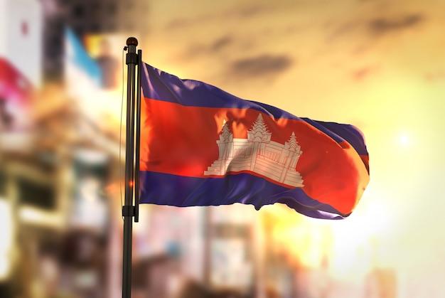 Bandeira do camboja contra a cidade fundo borrado no amanhecer luz de fundo Foto Premium
