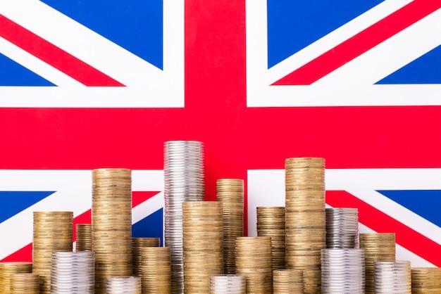 Bandeira do reino unido com pilhas de moedas de ouro e prata. símbolo da economia no reino unido Foto Premium