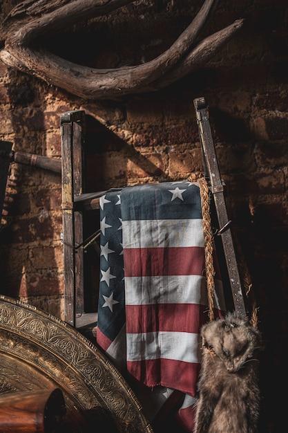Bandeira dos estados unidos pendurada em um suporte de metal em um sótão antigo Foto gratuita